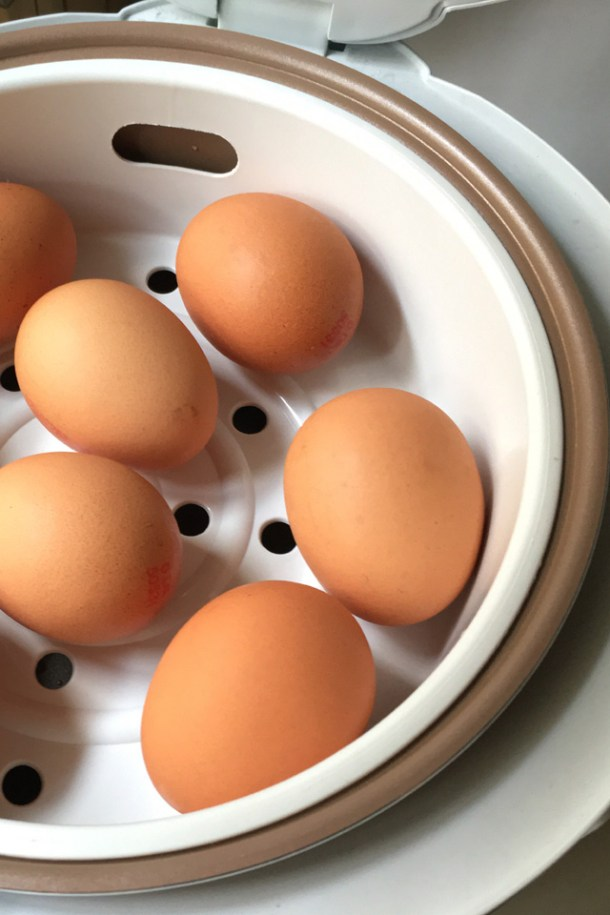 Close-up of brown eggs in a steaming tray in a rice cooker to Cook Eggs In A Rice Cooker