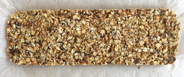 An uncut slab of Simple Nutty Granola Bars with rolled oats, nuts, and chocolate chips