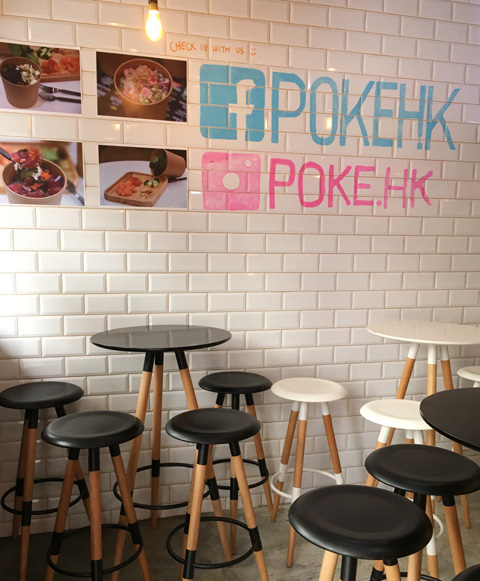 Black and white tables and stools inside Poke HK