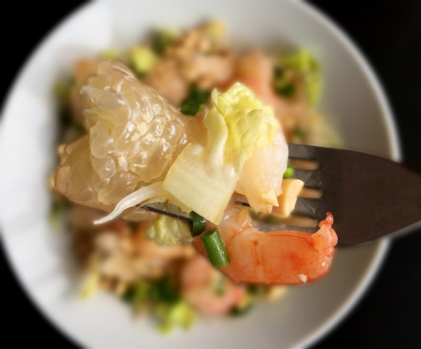 A forkful of Prawn Pomelo Salad with a pomelo wedge, lettuce, shrimp, chopped peanuts, and green onion