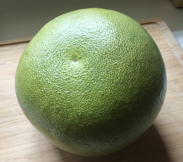 A whole green pomelo on a wooden cutting board