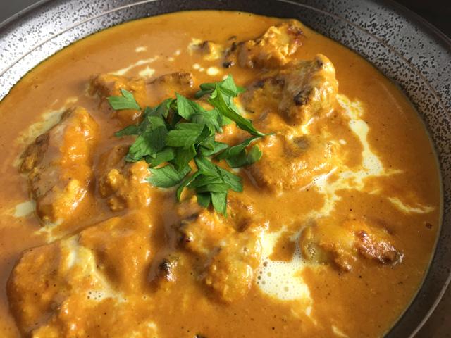A closeup of a metallic bowl of Creamy Butter Chicken