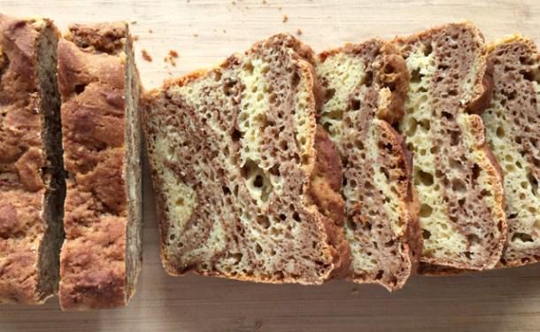 A sliced loaf of Gluten-Free Cinnamon Marble Bread on a cutting board