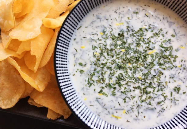 A pile of chips next to a bowl of creamy cucumber tzatziki