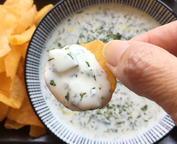 Close-up of a hand holding a chip dipped in creamy cucumber tzatziki
