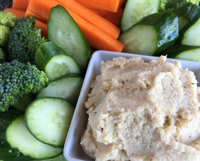 Raw cucumber slices, broccoli, and carrot sticks surrounding a dish of Roasted Cauliflower Hummus made using Easy Homemade Tahini.