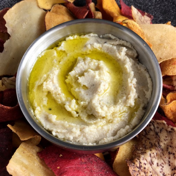 A silver bowl containing Roasted Cauliflower Hummus, surrounded by root chips.