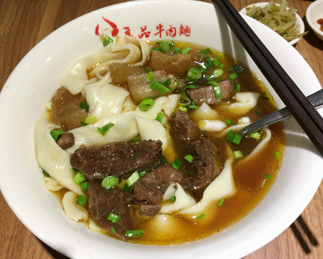 A white bowl of Taiwanese beef noodle soup with homemade noodles - eat in Taipei