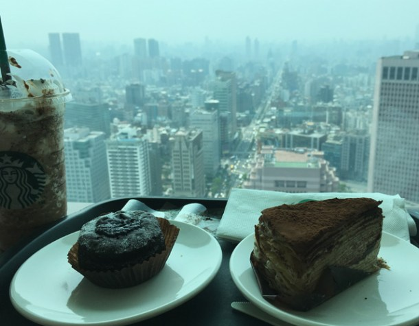 A closeup of Starbucks drinks and food with a view of Taipei in the background