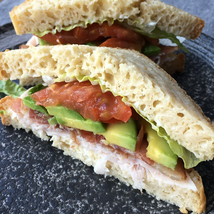 A round plate containing a sandwich filled with red tomatoes, green avocado, white meat