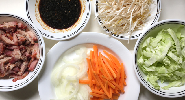 White dishes containing bbq pork, sliced onions, carrots, cabbage, beansprouts, and soy sauce