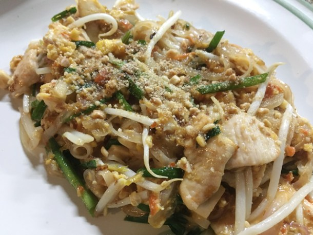A white plate of pad Thai containing noodles, green onions, bean sprouts, chicken, and peanuts in Chiang Mai