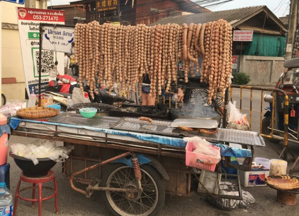 A cart on wheels, with a cooking grill and an assortment of meatballs and weiners at the Saturday Night Market in Chiang Mai