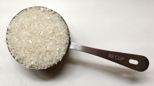 A stainless steel 1/2 cup measuring cup containing dry uncooked rice