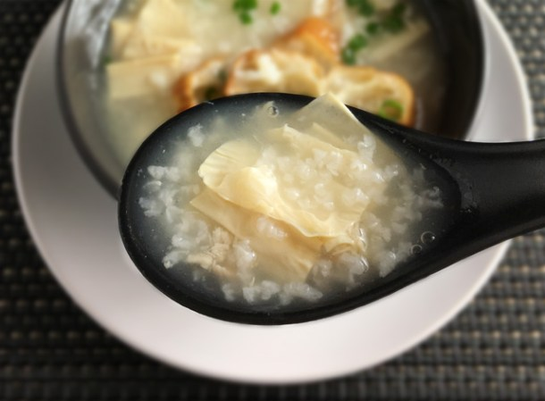 A closeup of a black spoon containing Chinese rice porridge congee and dried bean curd