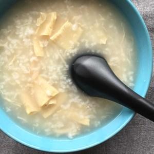 A black soup spoon in a blue bowl of rice porridge congee