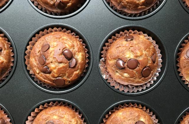 Banana chocolate chip muffins in a dark metal muffin pan