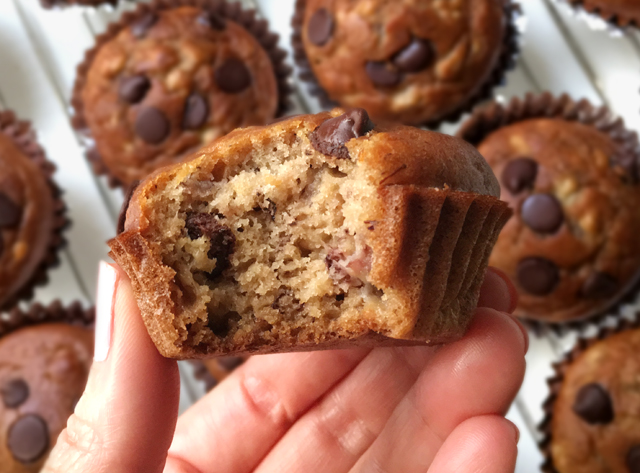 A hand holding a banana chocolate chip muffin with a bite taken out of it