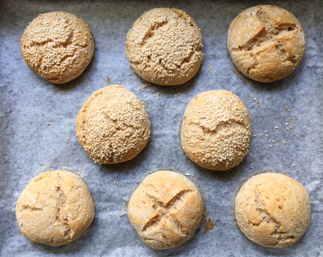 Eight gluten-free buns on a parchment paper lined baking sheet
