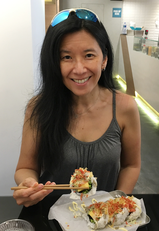 An Asian woman holding up a piece of maki sushi at Chotto Maki