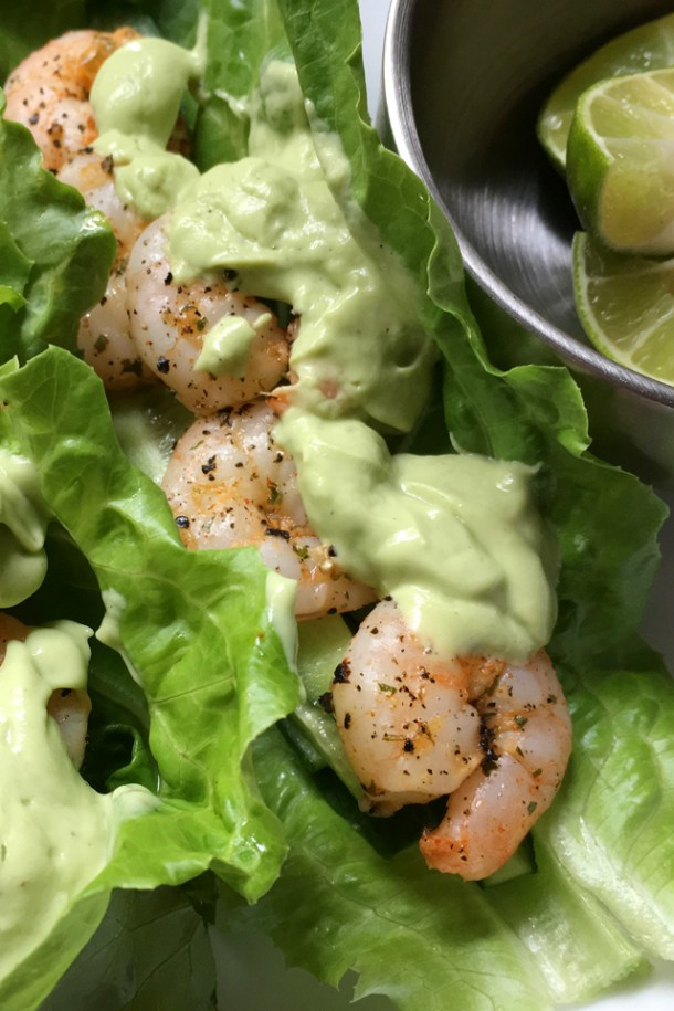 A lettuce shrimp taco with avocado crema next to a stainless steel bowl containing lime wedges