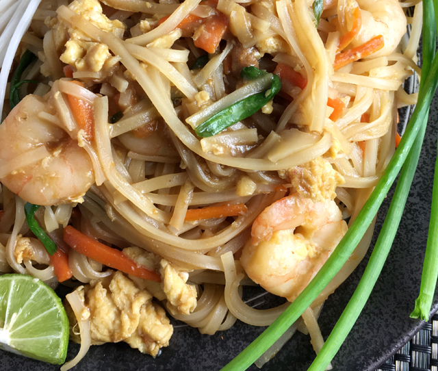 Close-up of a plate of shrimp pad thai with green onion stalks, cut lime, and white bean sprouts