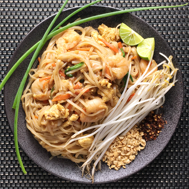 A dark round plate containing shrimp pad thai, white bean sprouts, crushed peanuts, red chili pepper flakes, and three green onion stalks