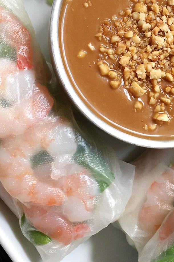 A closeup of fresh summer rolls next to a bowl of peanut sauce