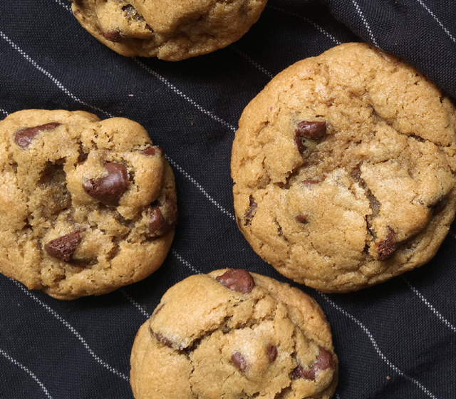 Four gluten-free chocolate chip cookies on a dark cloth with white pinstripes