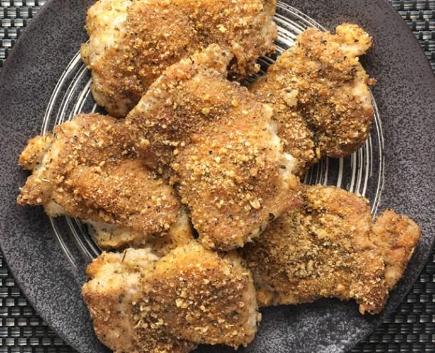 A dark grey round plate containing shake n bake chicken thighs