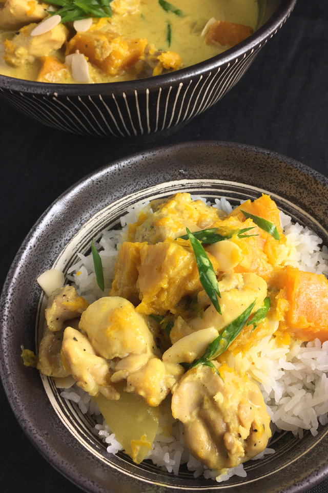 A small bowl containing chicken pumpkin curry on rice next to a large bowl of chicken pumpkin curry