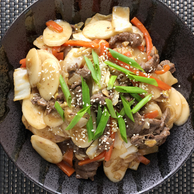 A black round dish containing stir-fried rice cakes topped with green onions and sesame seeds