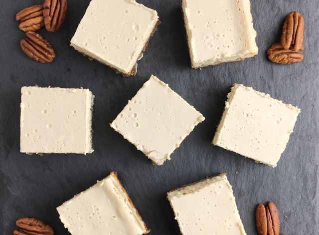 Overhead view of seven cheesecake squares and pecan halves on a grey stone platter