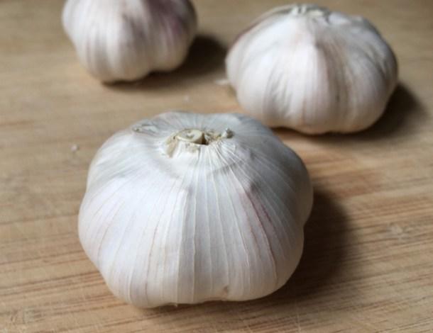 A wooden cutting board with 3 bulbs of raw garlic for roasted garlic