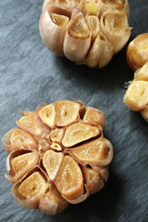 3 roasted garlic bulbs on a grey stone surface