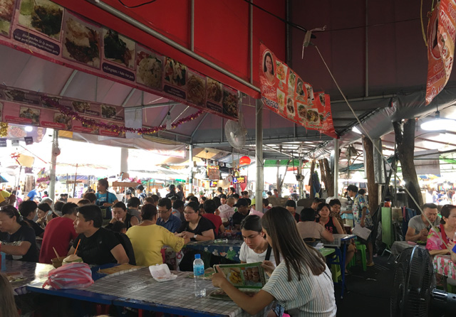 A crowd of people eating in a covered area at the Chatuchak Market, Bangkok