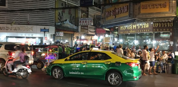 A yellow and green taxi driving by a large crowd of people