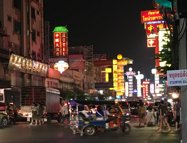 Many cars driving down a road lined with bright neon signs