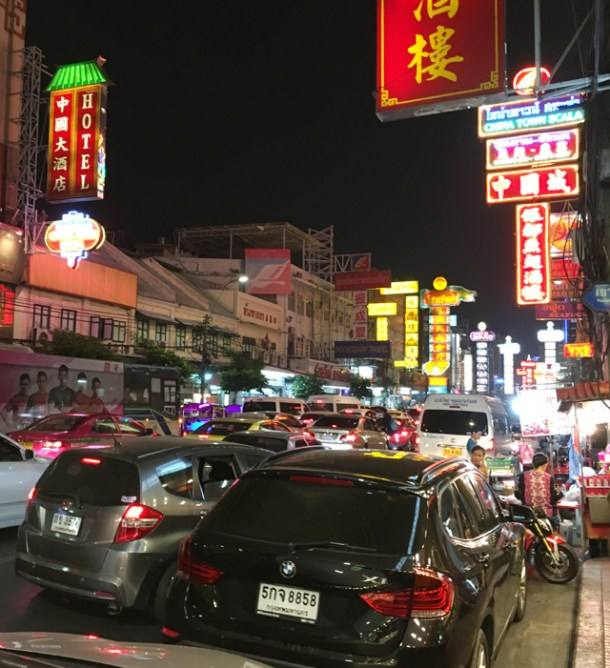A traffic jam of cars on a street lined with neon signs