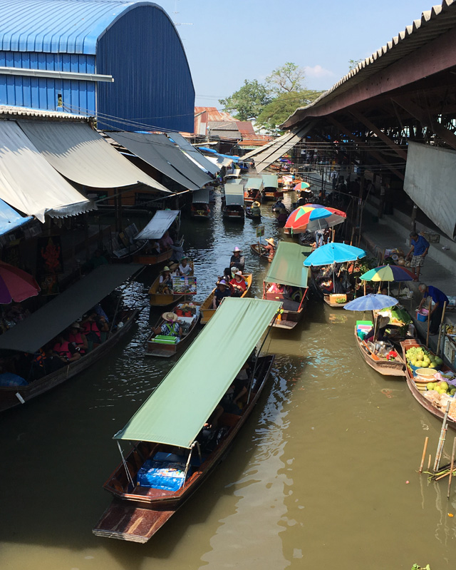 Long boats in a canal containing brown muddy water