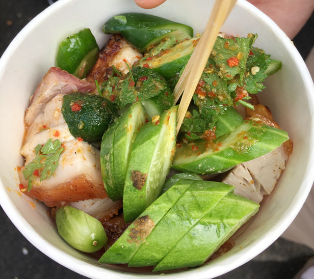 A round white bowl containing chunks of pork belly and cucumber slices