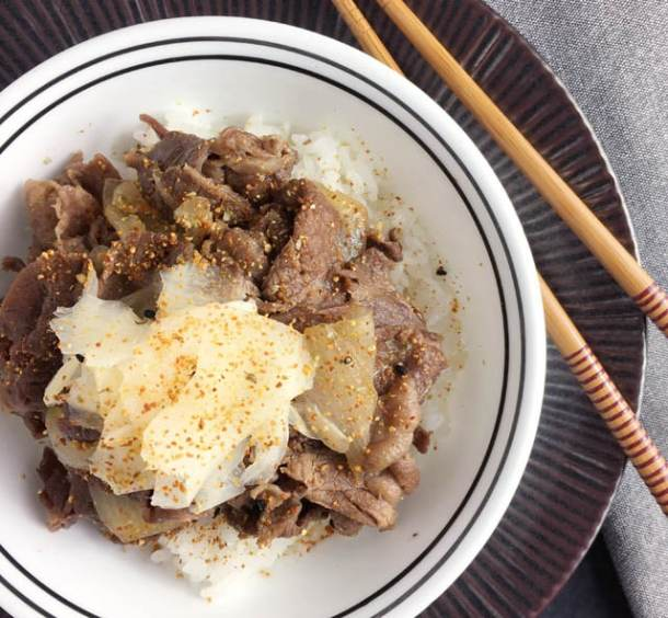 A white round bowl containing beef and onions on top of white rice for gyudon beef bowl