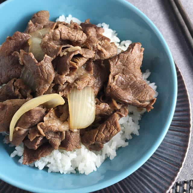 A round blue bowl containing gyudon beef bowl over white rice
