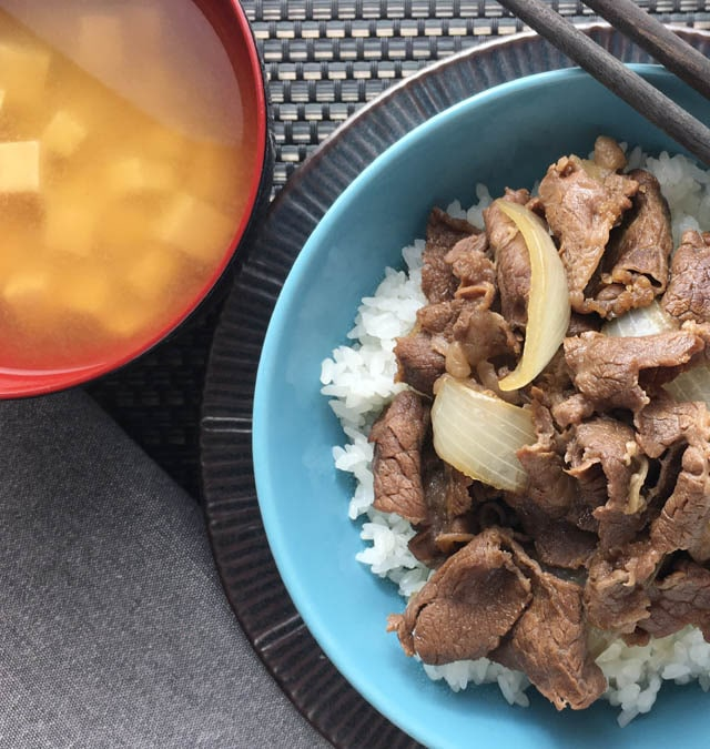 A red round bowl containing soup next to a blue bowl containing beef and onions for gyudon beef bowl