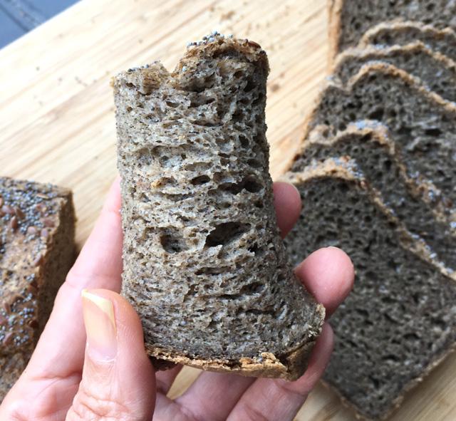 A hand holding a folded slice of buckwheat bread