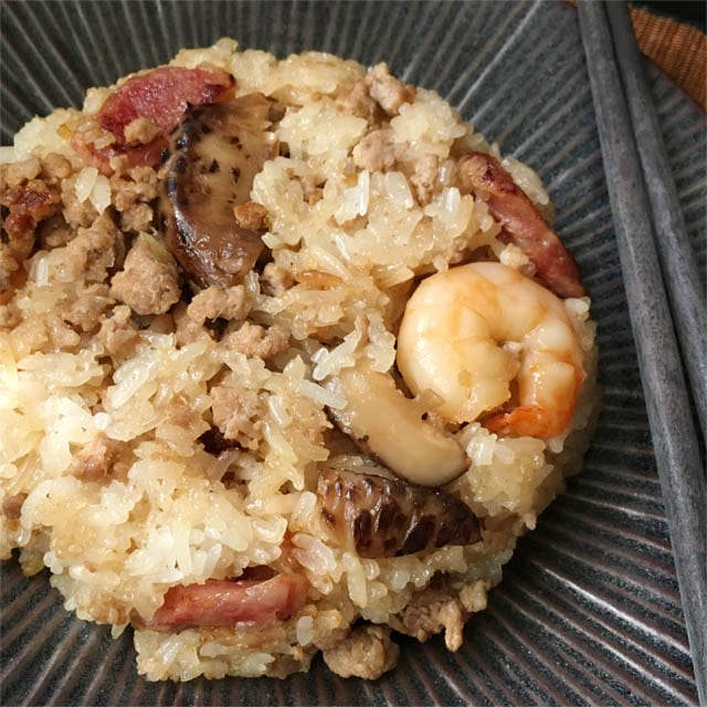A dark round plate containing rice mixed with mushrooms, shrimp, and red Chinese sausage