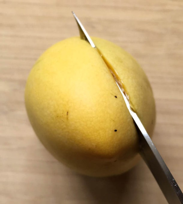 A knife slicing into a yellow mango set on a wooden cutting board