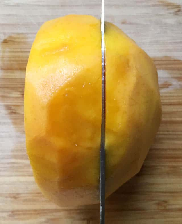 Close-up of a knife slicing a large chunk off a yellow orange mango