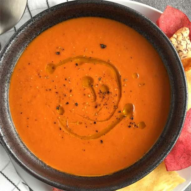 A dark round bowl containing orange roasted tomato soup with olive oil drizzle and cracked black pepper on top