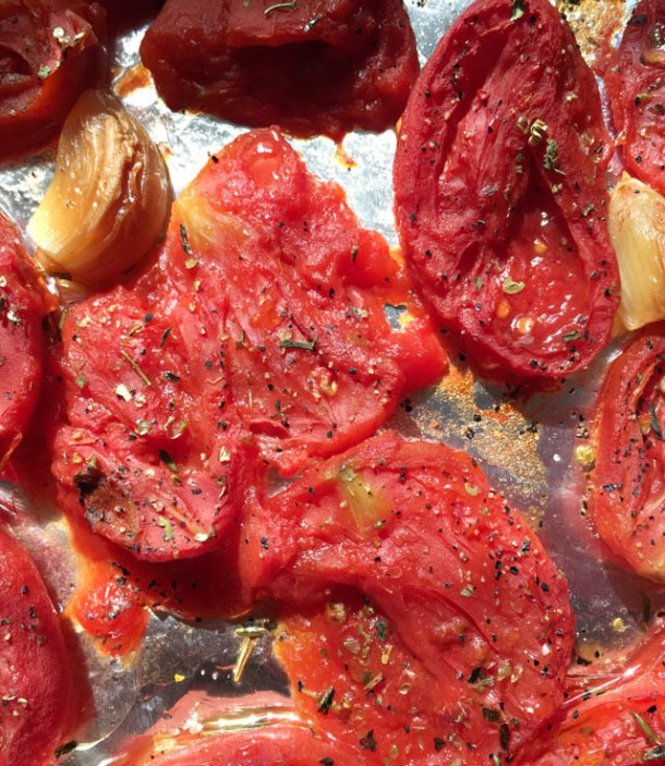 Red tomatoes and brown garlic cloves on a baking sheet for roasted tomato soup